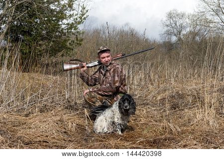 Oundoor shot of man with a gun and Russian hunting Spaniel.