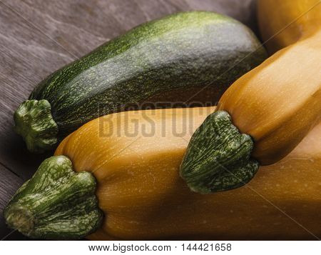Two yellow big and medium and small green zucchini on wooden table.Family of zuccini.Closeup