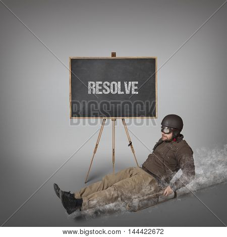 Resolve text on blackboard with businessman sliding with a sledge