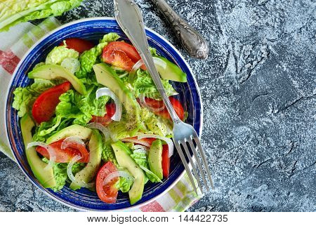 Salad with avocado tomato romaine lettuce and olive oil dressing