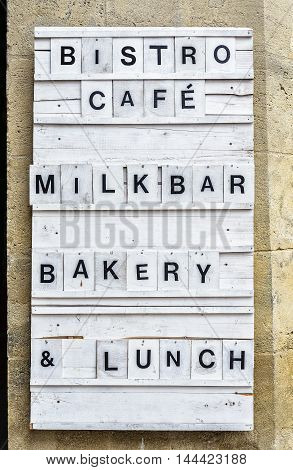 Bistro Wooden Panel On A Stone Wall.