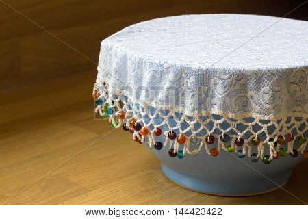 Beaded lace food protector covering a bowl
