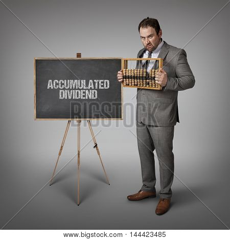 Accumulated Dividend text on blackboard with businessman and abacus