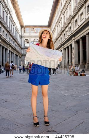 Young female traveler in hat and blue dress standing with paper map near famous Uffizi museum in Florence. Vacation in Italy