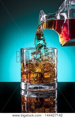 Pouring a glass of liqour from a glass bottle.