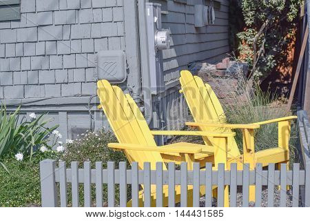 Santa Cruz, California, August 22, 2016 - two yellow Adirondack chairs behind a grey picket fence, mid-afternoon