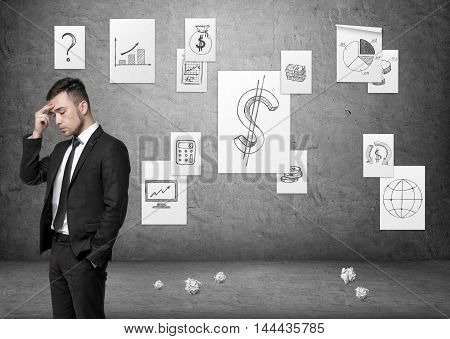 Businessman speculating on the background of concrete wall with business posters and pieces of paper on the floor. Thinking and pondering. Business plan. Brainstorming.