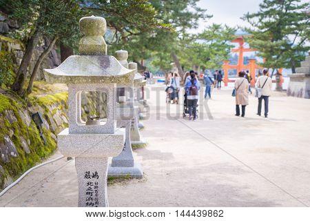Hiroshima, Japan - March 16, 2016: Tourists are traveling to the Temple on the Beach side walk of Miyajima island.