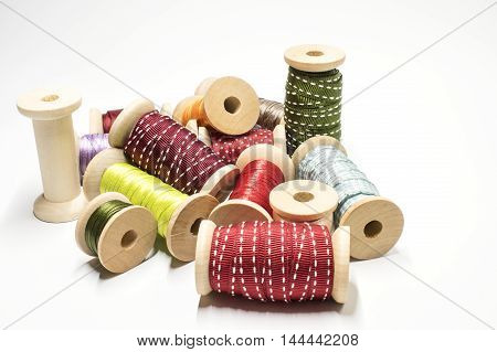 Wooden spools with colored ribbons on white