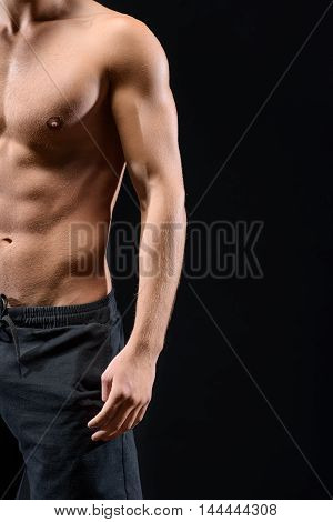 Close up of vertical half of male trained body. Young guy is standing with naked chest. Isolated and copy space in right side