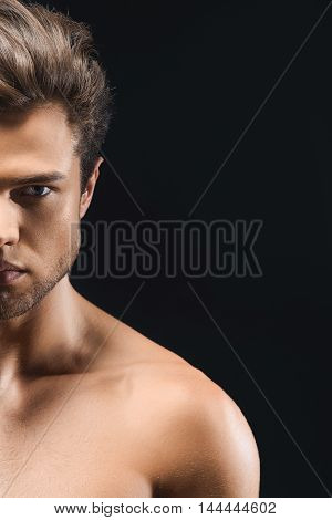 Passionate young man is standing with bare trained body. He has prefect skin. Macho is looking forward with desire. Isolated on black background