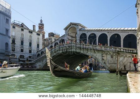 VENICE,ITALY-AUGUST 17,2014:Venetian gondoliers carry around some tourists on a gondola in Venice During a sunny day inside her famous canals.