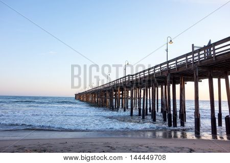 Surf waves near historic wooden pier in city of San Buena Ventura Southern California