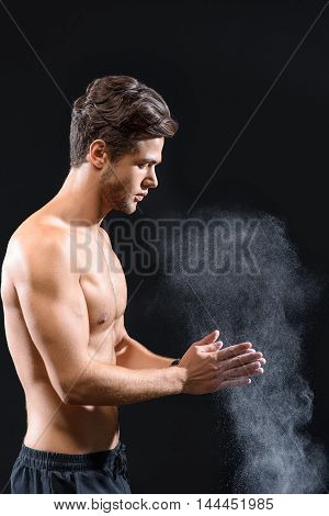 Confident young man is rubbing his hands with talc before training. He is standing with naked torso. Isolated on black background
