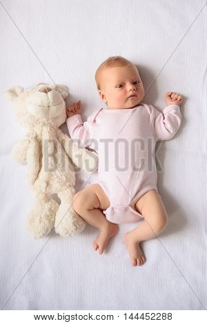 Curious little baby. High angle shot of cute baby lying on bed with teddybear beside her