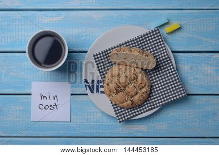 Inexpensive bun, a cup of coffee and two slices of sugar on a blue wooden table. The minimum cost.