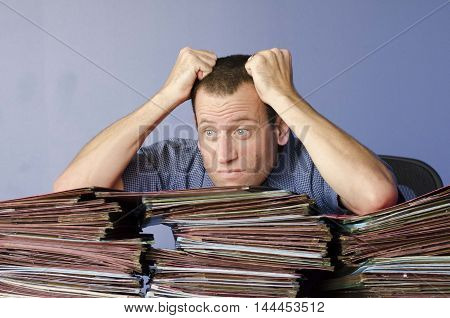 Man pulling his hair out, stressed at work with piles of files in front of him.