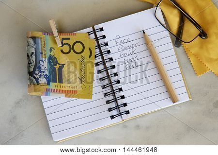 Shopping list in a notebook with Australian money and spectacles.