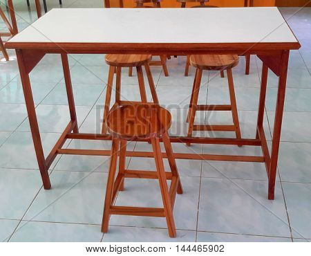 wooden lab table with braced legs, white formica top, and three varnished four-legged wooden stools, on pale blue tile floor, Ranot, Thailand
