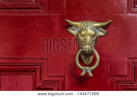 A metal bull settled on a red door