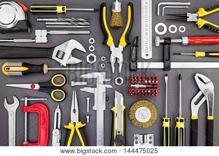 Various Working Tools On Grey Table Background. Drills, Wrenches, Bolts, Screws, Clamps