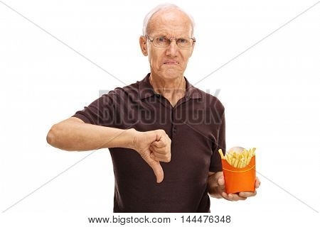 Senior man holding a bag of fries and making a thumb down gesture isolated on white background