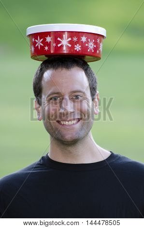 Happily juggling but balancing the Holiday Season - man with a smile on his face and a Christmas container on his head.