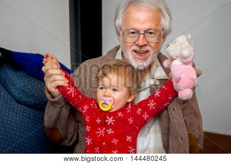 A baby girl sits in the lap of her grandfather with arms raised high and a pacifier in her mouth. She is holding a stuffed animal and is wearing her Christmas pajamas.