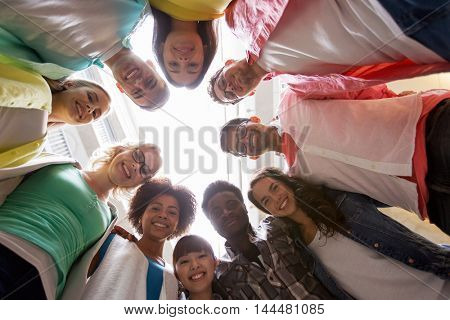 education, school, friendship and unity people concept - group of happy international students standing in circle