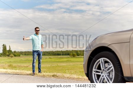 road trip, hitchhike, travel, gesture and people concept - man hitchhiking and stopping car with thumbs up gesture at countryside road