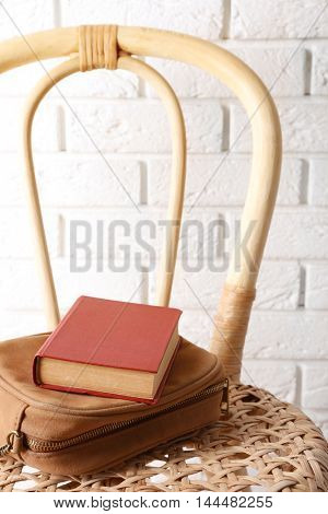 Book with handbag on wicket chair