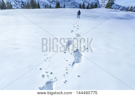 A man's footprints on the snow - Winter scenery with lots of snow a man heading to the mountains leaving footsteps behind.