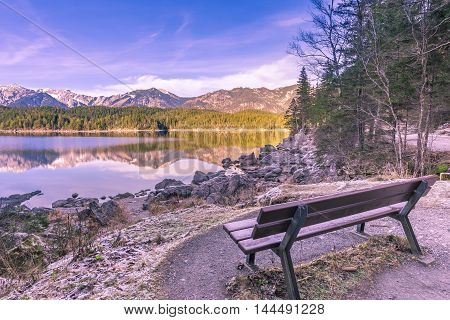 Bench on the shore of an alpine lake - Winter image with a bench located on the shore of the Eibsee lake from Grainau Germany. Reflected in its water are the Bavarian Alps mountains.