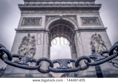Chain links and the Arc de Triomphe in the background - Metaphoric image with chain links sprinkled with rain drops in the foreground and the Arc de triumph on the background in Paris France.