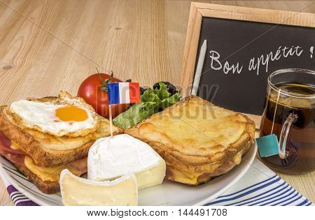 French dish with message on chalkboard - Traditional french sandwiches croque madame and croque monsieur fine cheese and fresh salad placed on table and near it a chalkboard with the message of bon appetit.