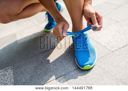 Woman fixing runnning shoes