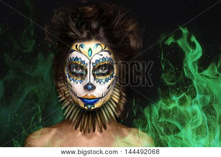 photo portrait of halloween girl in image of dead mexican goddess Los Muertos in green fire, dark art photo in studio, creative makeup
