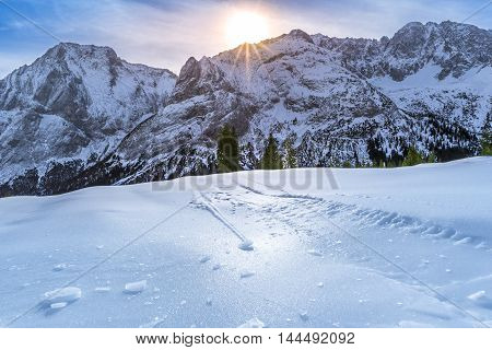 Ice crust over snowy mountains and pastures - Alpine scenery on a bright day of winter with details over the crust of ice that lies on the surface of the Austrian Alps pastures and is due to the warmth of the sun that shines from behind the rocky peaks.