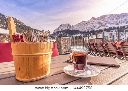 Outdoor table restaurant with cutlery and hot drink - Image with a cup of hot drink a menu and a rustic holder of cutlery on a wooden table with mountains in the background. Picture taken in Austria.