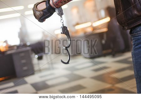 Hand male in unbuttoned handcuffs, on background of the police station