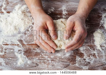 Bakers male hands prepares the dough for bread or pizza on a wooden table. Rustic style, top view.