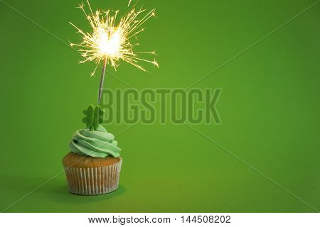 Tasty cupcake with sparkler on green background. Saint Patrics Day concept