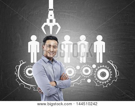 Smiling Asian man standing near blackboard with conveyor belt sketch. Concept of recruiting agency