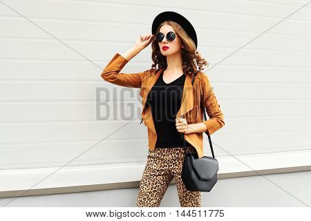 Fashion Pretty Woman Wearing A Retro Elegant Hat, Sunglasses, Brown Jacket And Black Handbag Walking