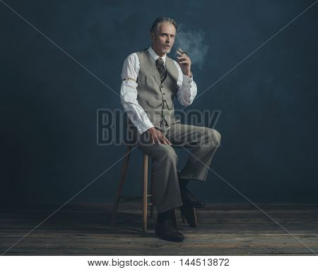 Cigar Smoking Retro 1920S Man Wearing Suit Sitting On Wooden Stool. Empty Room. Vintage Wooden Floor