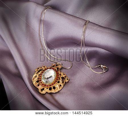 Stone fitten antique golden pendant on gery drapery