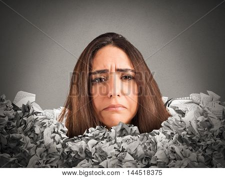 Sad woman trapped in a mountain of paperwork