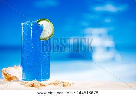 blue slush ice drink in glass on sea beach background