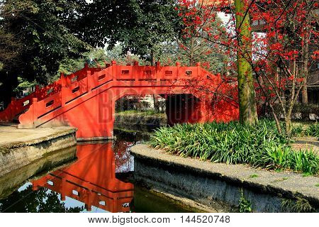 Pixian China - Febuary 23 2009: A beautiful orange bridge over a canal in Wang Cong Ci Park with flowering Quince tree on the right