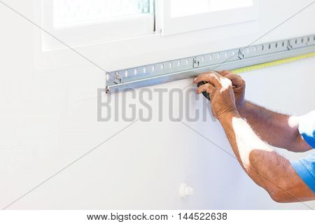 Asian Mans Measuring A Wall With Measure Tape Preparing To Build Kitchen Counter